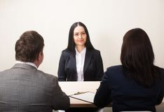 Jovem mulher durante a entrevista de trabalho e os membros dos managemen imagem de stock