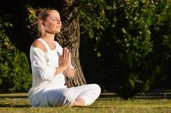 Jovem mulher durante a meditação da ioga no parque Foto de Stock