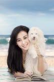 Jovem mulher e cão que encontram-se na costa foto de stock