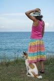 Jovem mulher e cão que olham o mar Imagem de Stock Royalty Free