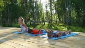 Jovem mulher e crianças que praticam a ioga filme