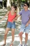 Jovem mulher e homem cego que andam no parque fotografia de stock