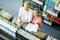 Jovem mulher e homem na biblioteca Imagem de Stock