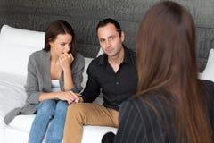 Jovem mulher e homem na terapia dos pares interna fotos de stock royalty free