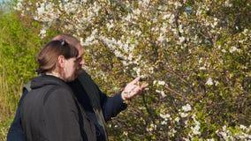 Jovem mulher e homem perto de uma árvore de florescência filme
