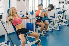 Jovem mulher e homem que dão certo no gym Pares que fazem exercícios para os braços Corpos perfeitos imagens de stock royalty free