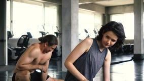 Jovem mulher e homem que esticam seus p?s no assoalho do gym Dois pessoas dar certo dos pares interno filme