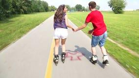 Jovem mulher e homem que rollerblading e que executam no parque em um dia morno bonito, guardando as mãos filme