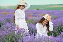 A jovem mulher e a menina estão no campo da alfazema, paisagem bonita do verão com as flores vermelhas da papoila fotografia de stock