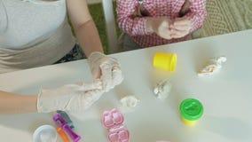 A jovem mulher e a menina moldam seus dentes do plasticine, do jogo no dentista, da mãe e da filha filme
