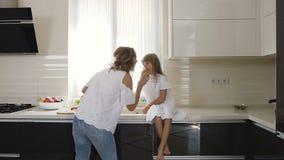 A jovem mulher e a menina vestiram-se na roupa que do branco o divertimento come a maçã vermelha deliciosa em casa na cozinha Mam vídeos de arquivo
