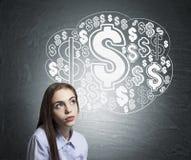 Jovem mulher e nuvem sonhadoras do sinal de dólar foto de stock