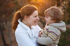 A jovem mulher e o filho pequeno que abraçam na noite iluminam-se Fotos de Stock