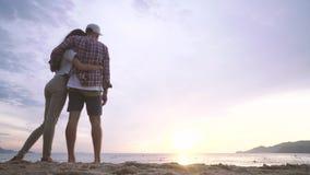 A jovem mulher e o homem abraçam-se na praia e olham-se ao por do sol sobre o mar filme