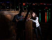 A jovem mulher e o homem estão ao leme do navio e olham o th imagem de stock