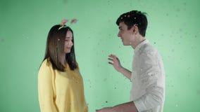 A jovem mulher e o homem estão dançando em um confete colorido em um fundo verde filme