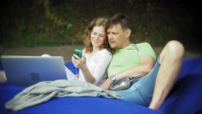 A jovem mulher e o homem maduro usam um portátil, encontrando-se em uma área da sala de estar do parque em sopros macios filme
