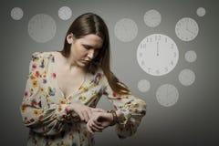 Jovem mulher e relógio de pulso 12 p M Imagem de Stock