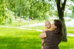 Jovem mulher e seu bebê bonito exteriores fotografia de stock royalty free
