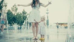 Jovem mulher e seu bebê pequeno que têm o divertimento na fonte do parque da cidade, movimento lento vídeos de arquivo
