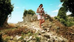 A jovem mulher e seu bebê que viajam com portador backpack em férias vídeos de arquivo