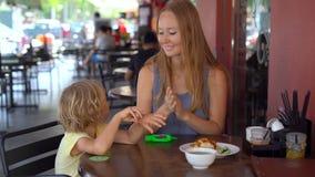 A jovem mulher e seu filho usam um sanitizer da mão em um café filme