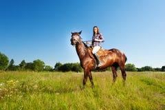 Jovem mulher e seu garanhão marrom em um prado foto de stock royalty free