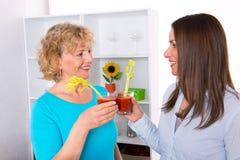 Jovem mulher e seu suco de tomate bebendo da mãe junto no Fotos de Stock Royalty Free