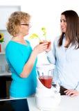 Jovem mulher e seu suco de tomate bebendo da mãe junto no Imagem de Stock