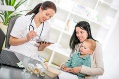 Jovem mulher e sua criança nos homeopata do doutor imagem de stock royalty free