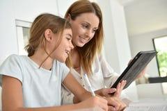 Jovem mulher e sua filha que usa a tabuleta foto de stock