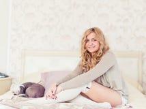 Jovem mulher e um cão que senta-se em uma cama Foto de Stock Royalty Free