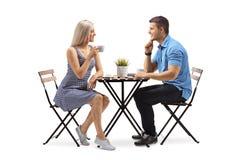 Jovem mulher e um homem novo assentado em uma mesa de centro Imagem de Stock