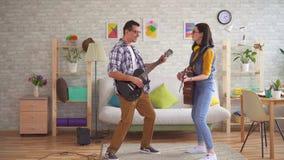 A jovem mulher e um homem novo jogam emocionalmente guitarra e dança