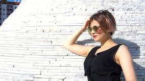 Jovem mulher elegante à moda nos óculos de sol em um vestido preto exterior vídeos de arquivo
