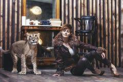 Jovem mulher elegante bonita com um filhote de leão vivo pequeno Fotos de Stock