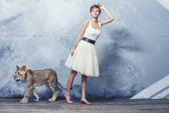 Jovem mulher elegante bonita com um filhote de leão vivo pequeno Foto de Stock