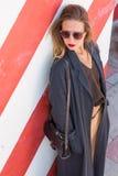 A jovem mulher elegante bonita está estando perto da parede listrada com um saco e um revestimento longo Fotos de Stock Royalty Free