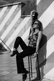 A jovem mulher elegante bonita está sentando-se em uma cadeira perto da parede listrada Fotografia de Stock Royalty Free