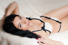 Jovem mulher elegante bonita 'sexy' que coloca na roupa interior ou no biquini vestindo da cama Foto de Stock