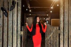 A jovem mulher elegante com cabelo moreno longo e no vestido vermelho está e olha para baixo fotografia de stock royalty free