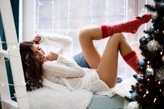 Jovem mulher elegante em um equipamento vermelho festivo do Natal que encontra-se em sua sala de visitas que aprecia o Natal fotos de stock