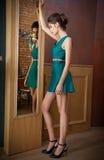 Jovem mulher elegante no vestido curto que olha em um grande espelho, vista lateral de turquesa Menina magro bonita com penteado  fotos de stock