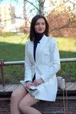 Jovem mulher elegante que levanta em uma rua da cidade com um jornal e no m?bil em suas m?os fotografia de stock