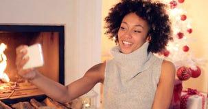 Jovem mulher elegante que toma um selfie do Natal imagens de stock