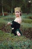 A jovem mulher elegante vestiu-se como a rainha que anda no jardim Imagem de Stock