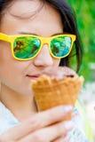 Jovem mulher em óculos de sol amarelos com um gelado Imagens de Stock