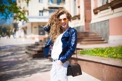 Jovem mulher em óculos de sol e no casaco de cabedal redondos do moderno com Fotografia de Stock