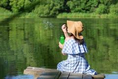 Jovem mulher em bolhas de sopro de um vestido e de um chapéu de palha contra t imagens de stock