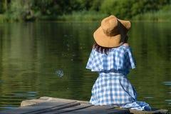 Jovem mulher em bolhas de sopro de um vestido e de um chapéu de palha contra t foto de stock royalty free